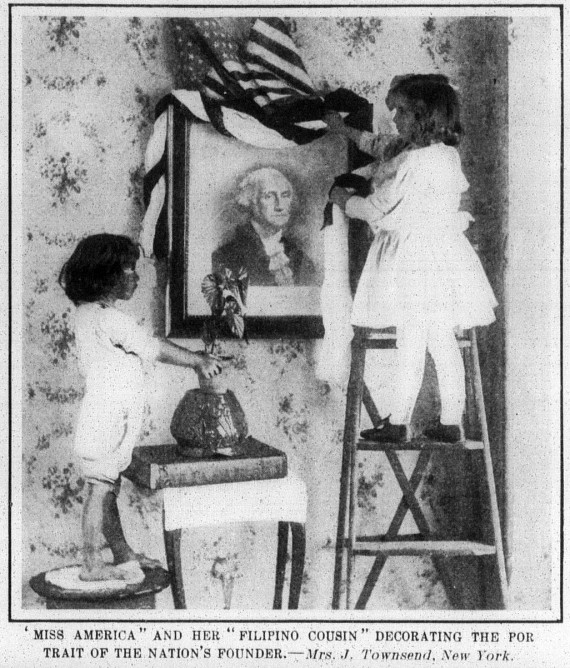 """""""MISS AMERICA"""" AND HER """"FILIPINO COUSIN"""" DECORATING THE PORTRAIT OF THE NATION'S FOUNDER.— Mrs. J. Townsend, New York ."""