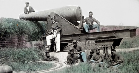 Lieutenant Samuel K. Thompson of Co. C, 54th U.S. Colored Troops Infantry Regiment with unidentified soldiers posed with a Columbiad cannon at an earthwork fort. (1863)